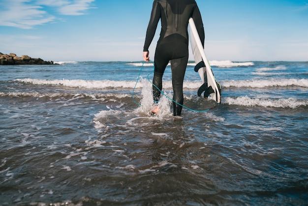 Junger surfer, der mit seinem surfbrett in einem schwarzen surfanzug ins wasser tritt. sport- und wassersportkonzept.