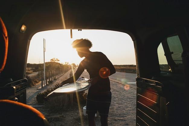 Junger surfer mit afro-haar, der ein surfbrett im wohnwagen fängt