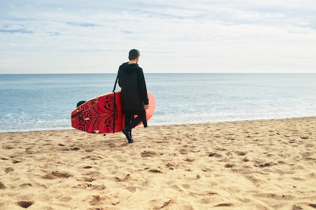 Junger surfermann am strand mit surfbrett