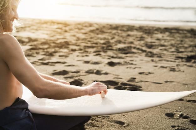 Junger surfermann, der sich für surf-sitzung bereit macht - fokus auf hand, die wachs hält