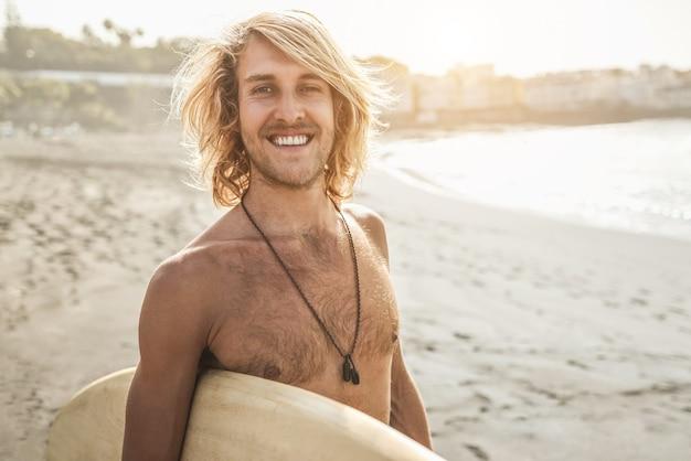 Junger surfermann, der surfbrett am strand bei sonnenuntergang hält - fokus auf gesicht