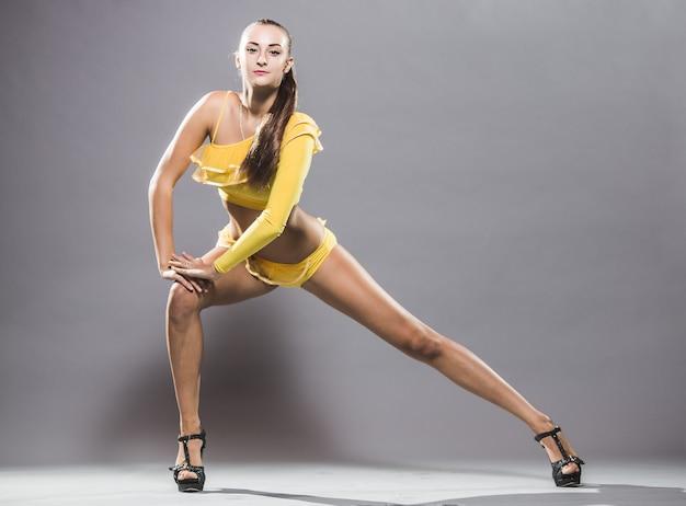 Junger tänzer mit einem sportkörper, der im studio auf einem weißen hintergrund aufwirft