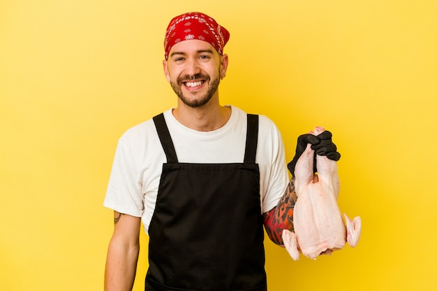 Junger tätowierter kaukasischer batcher-mann, der ein huhn lokalisiert auf gelbem hintergrund glücklich, lächelnd und fröhlich hält.