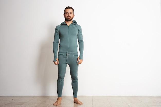 Junger taillierter bärtiger mann trägt eine suite mit thermischer basisschicht und steht vor einer weißen wand