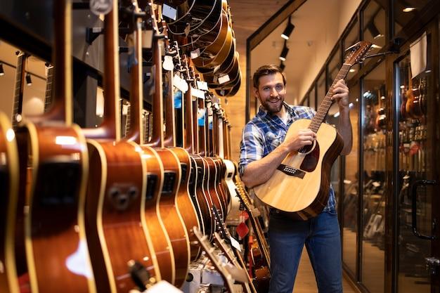 Junger talentierter gitarrist testet neues gitarreninstrument im musikladen.