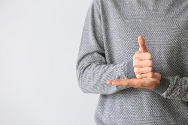Junger taubstummer mann mit gebärdensprache auf lgrey