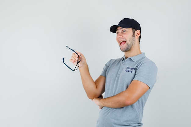 Junger techniker, der brille in grauer uniform hält und optimistisch schaut.