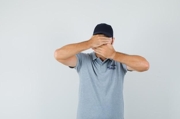 Junger techniker, der hände auf augen und mund in grauer uniform hält und ängstlich aussieht.