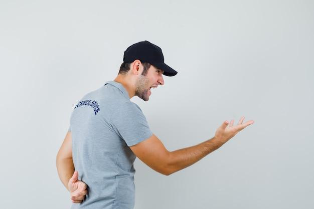 Junger techniker, der hand in fragender weise in grauer uniform streckt und wütend aussieht.