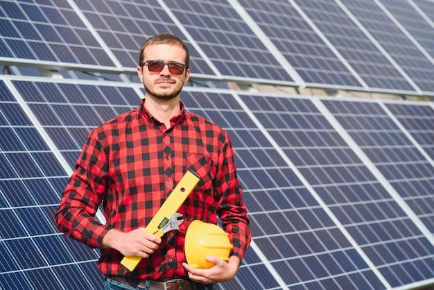 Junger techniker, der sonnenkollektoren auf fabrikdach installiert