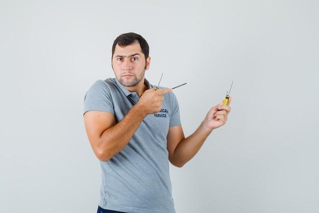 Junger techniker hält schraubendreher in beiden händen und zeigt auf sie in grauer uniform und sieht ernst aus.