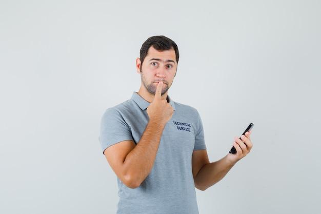 Junger techniker in der grauen uniform, die in der denkenden haltung steht, während telefon hält und nachdenklich schaut.