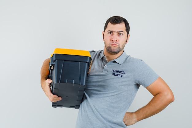 Junger techniker in der grauen uniform, die werkzeugkasten hält, während er seine hand auf taille hält und ernst aussieht.