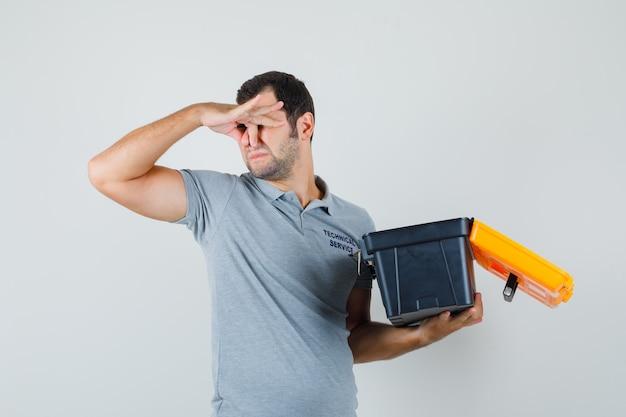 Junger techniker in grauer uniform hält geöffneten werkzeugkasten, während er sich wegen schlechten geruchs die nase kneift und genervt aussieht.