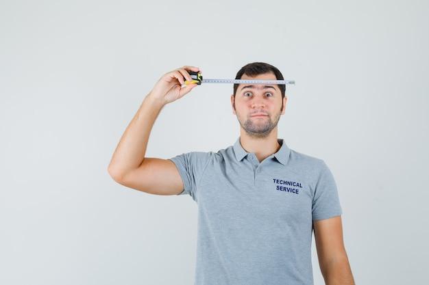 Junger techniker in grauer uniform hält maßband gegen seinen kopf und sieht ernst aus.