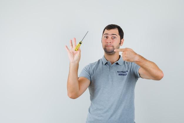 Junger techniker in grauer uniform hält schraubendreher in einer hand und zeigt darauf und sieht ernst aus.