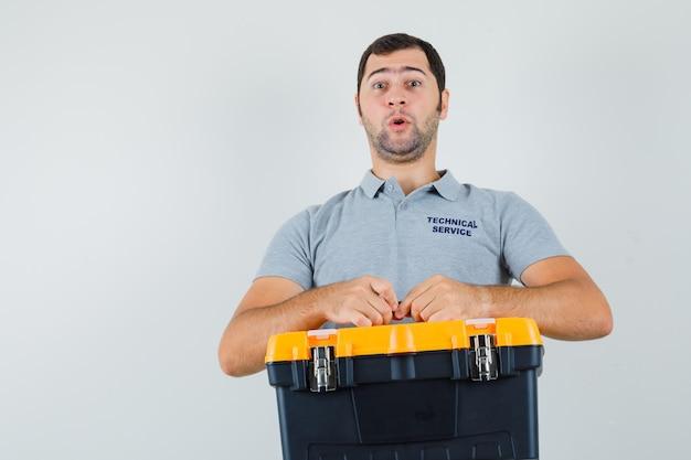 Junger techniker in grauer uniform hält werkzeugkasten mit beiden händen und sieht überrascht aus.