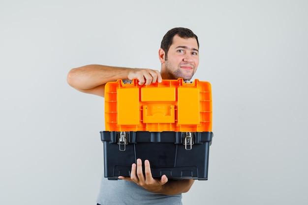 Junger techniker in grauer uniform öffnet werkzeugkasten mit beiden händen und sieht optimistisch aus.