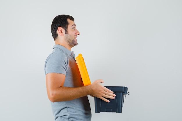 Junger techniker in grauer uniform trägt mit beiden händen einen geöffneten werkzeugkasten und sieht optimistisch aus.