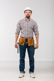 Junger techniker mit werkzeuggürtel auf seiner taille, der vor kamera steht und sie isoliert betrachtet
