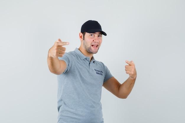 Junger techniker zeigt in grauer uniform weg und sieht munter aus.