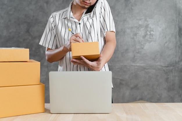 Junger teenager als freiberufliche arbeit mit laptop-computer und verpackung des postpaketkastens im wohnzimmer zu hause