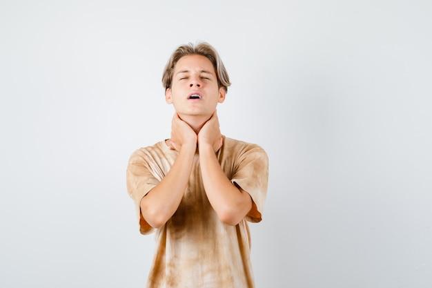 Junger teenager, der die hände am hals hält, die augen im t-shirt schließt und hoffnungsvoll aussieht. vorderansicht.
