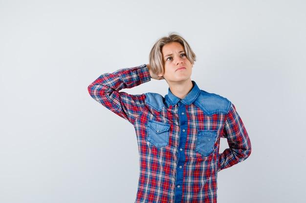 Junger teenager, der die hand hinter dem kopf hält, im karierten hemd aufschaut und nachdenklich aussieht. vorderansicht.