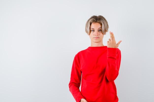 Junger teenager, der eine pistolengeste im roten pullover zeigt und ernst aussieht, vorderansicht.