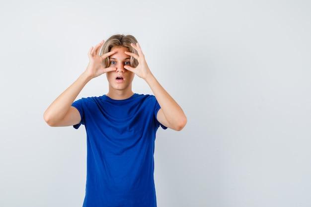 Junger teenager, der im blauen t-shirt durch die finger späht und verwundert schaut. vorderansicht.