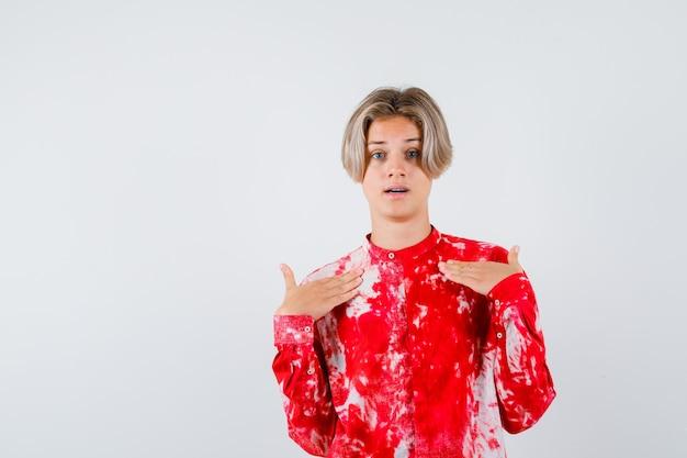 Junger teenager, der im hemd auf sich selbst zeigt und verwirrt schaut. vorderansicht.