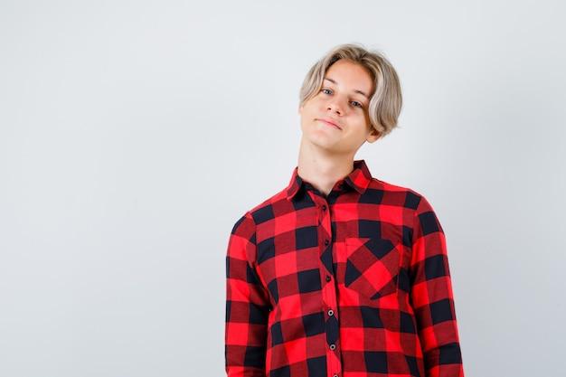 Junger teenager, der im karierten hemd vorne schaut und fröhlich aussieht. vorderansicht.