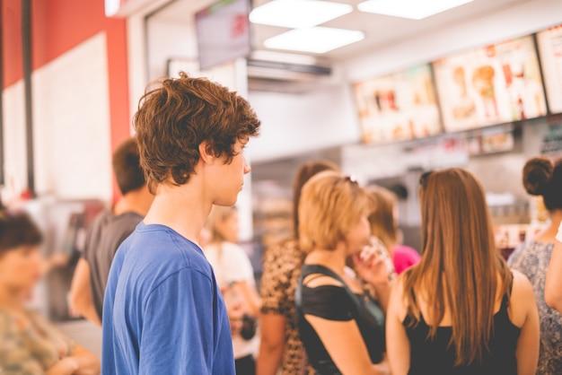 Junger teenager, der in einer warteschlange steht, um das fastfood zu erhalten