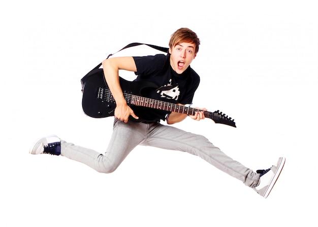 Junger teenager, der mit gitarre springt