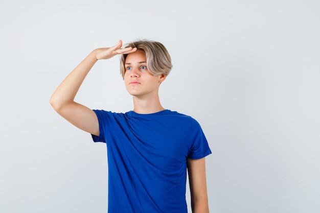 Junger teenager, der weit weg mit der hand über dem kopf in blauem t-shirt schaut und konzentriert aussieht, vorderansicht.