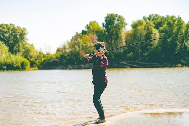 Junger teenager fischer in lässig fangen fische am ufer des flusses mit stange an einem sommertag