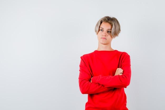 Junger teenager im roten pullover, der die arme verschränkt hält, wegschaut und nachdenklich aussieht, vorderansicht.