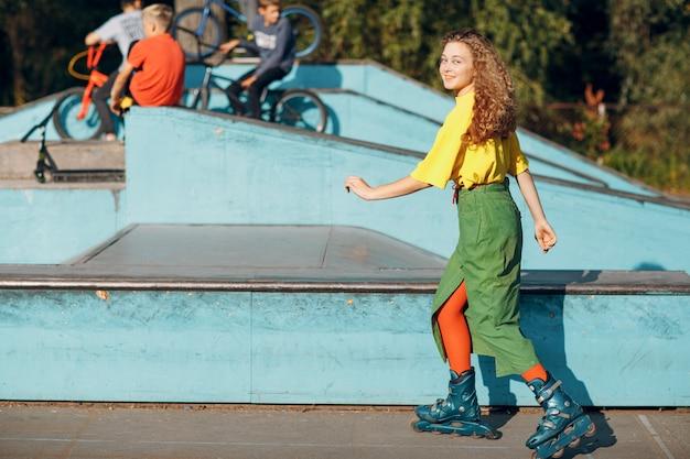 Junger teenager in der grünen und gelben kleidung und in den orangefarbenen strümpfen mit dem rollschuhlaufen der lockigen frisur im skatepark