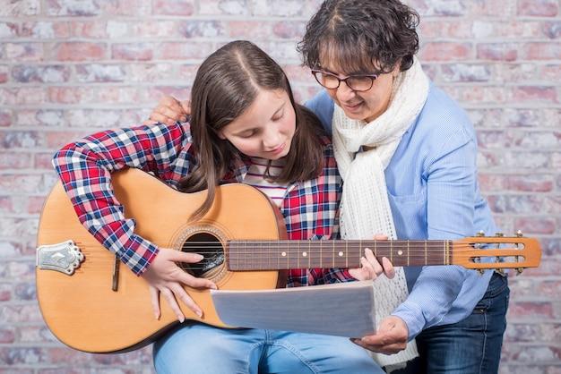 Junger teenager lernt mit seinem lehrer gitarre zu spielen