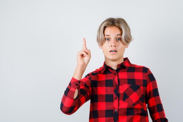 Junger teenagerjunge, der im karierten hemd nach oben zeigt und verwirrt schaut. vorderansicht.