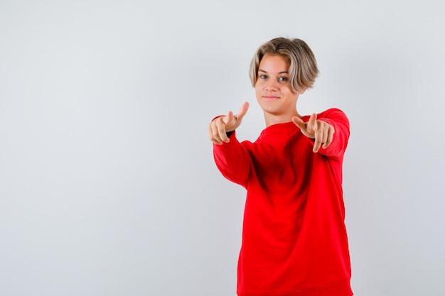 Junger teenagerjunge, der in rotem pullover nach vorne zeigt und nach vorne schaut. vorderansicht.