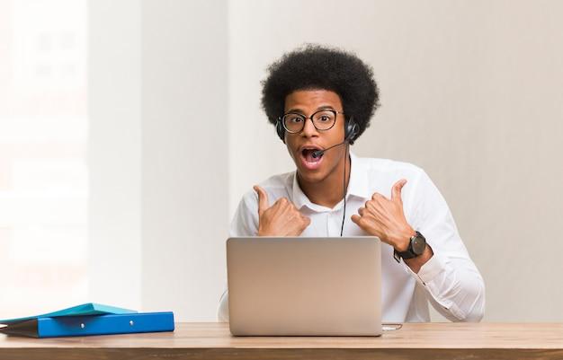 Junger telemarketer schwarzer mann überrascht, fühlt sich erfolgreich und wohlhabend
