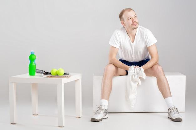 Junger tennisspieler mit handtuch, der sich nach dem training ausruht