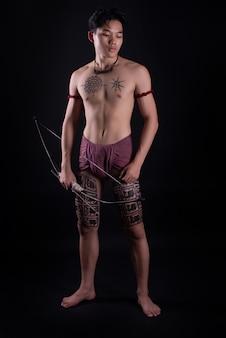 Junger thailand männlicher krieger, der in einer kämpfenden position mit einem bogen aufwirft