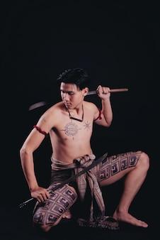 Junger thailand männlicher krieger, der in einer kämpfenden position mit einem schwert aufwirft