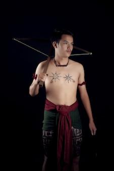 Junger thailand männlicher krieger, der in einer kämpfenden position mit einer armbrust aufwirft