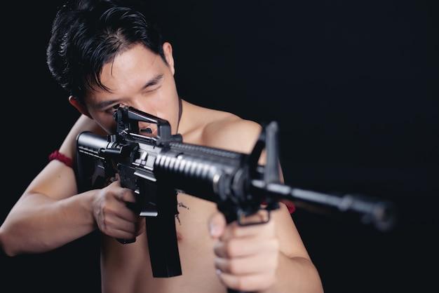 Junger thailand männlicher krieger, der in einer kämpfenden position mit einer feuerwaffe auf schwarzem aufwirft
