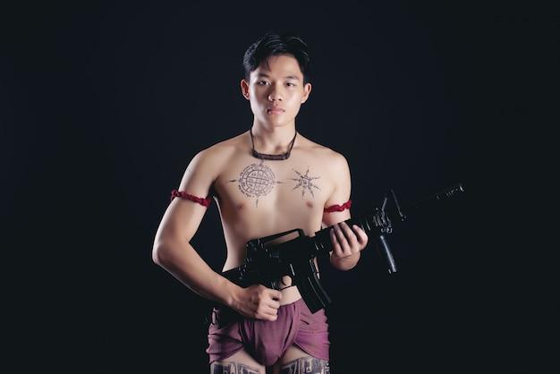 Junger thailand männlicher krieger, der in einer kämpfenden position mit einer feuerwaffe aufwirft