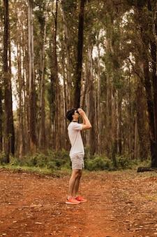 Junger tourist, der bäume mit fernglas beobachtet. wanderer im dschungel schaut sich um.