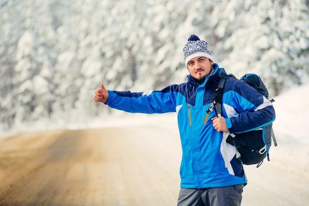 Junger tourist im winter, der auf der autobahn steht und das auto fängt